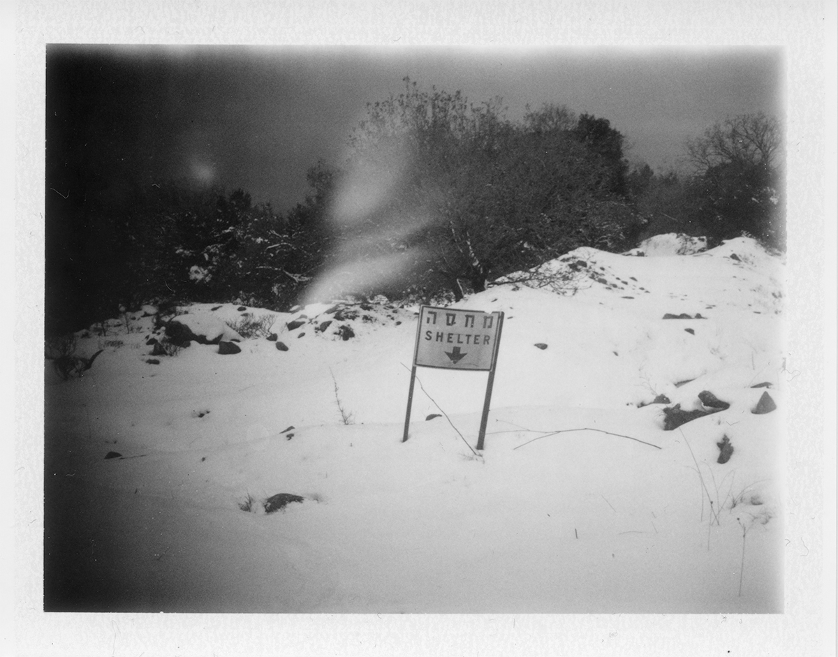 Black and white photo of sign reading 'shelter' in a snowy field