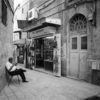 Black and white square photo of man sitting in an alleyway in the old city of Jerusalem
