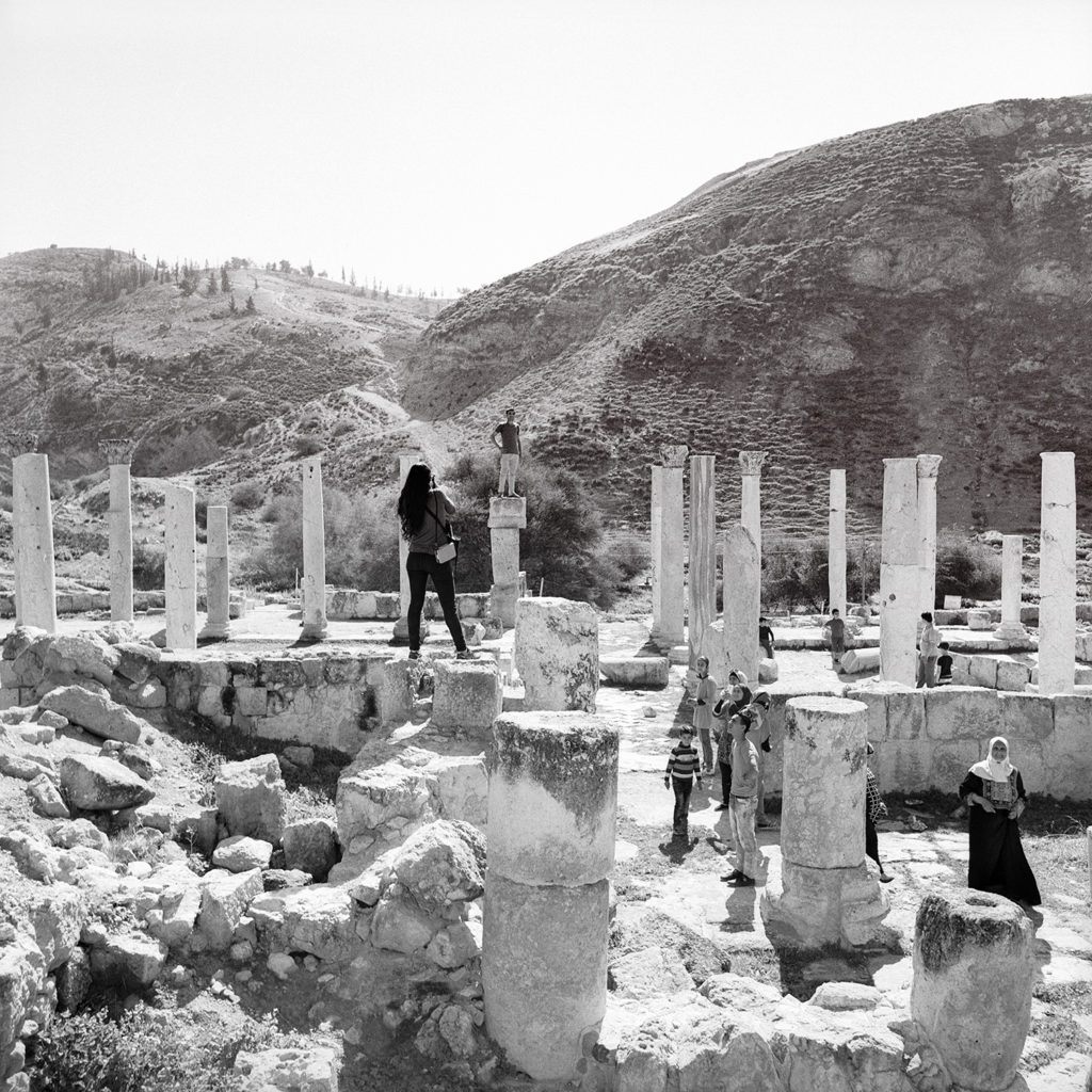 Black and white square photo of photographer standing on old Roman ruins taking a portrait with onlookers watching