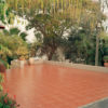 brick colored ceramic-floor driveway surrounded by greenery
