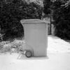 Black and white square photo of trashcan