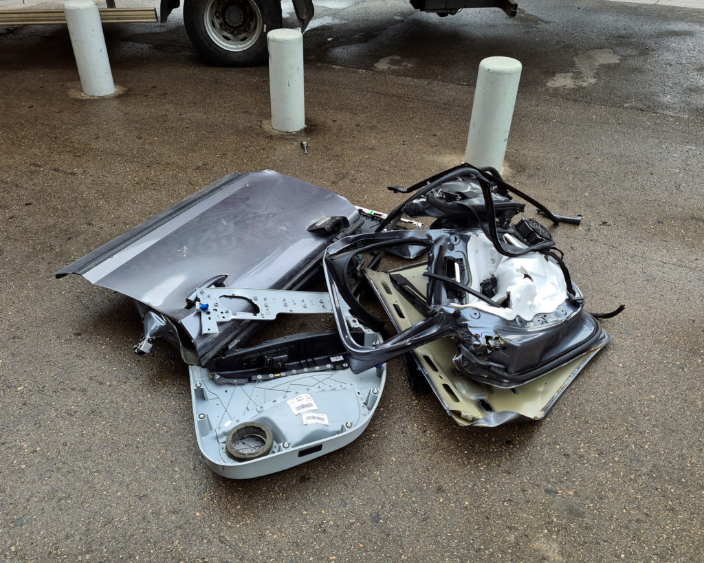 Car door and parts lay on the ground